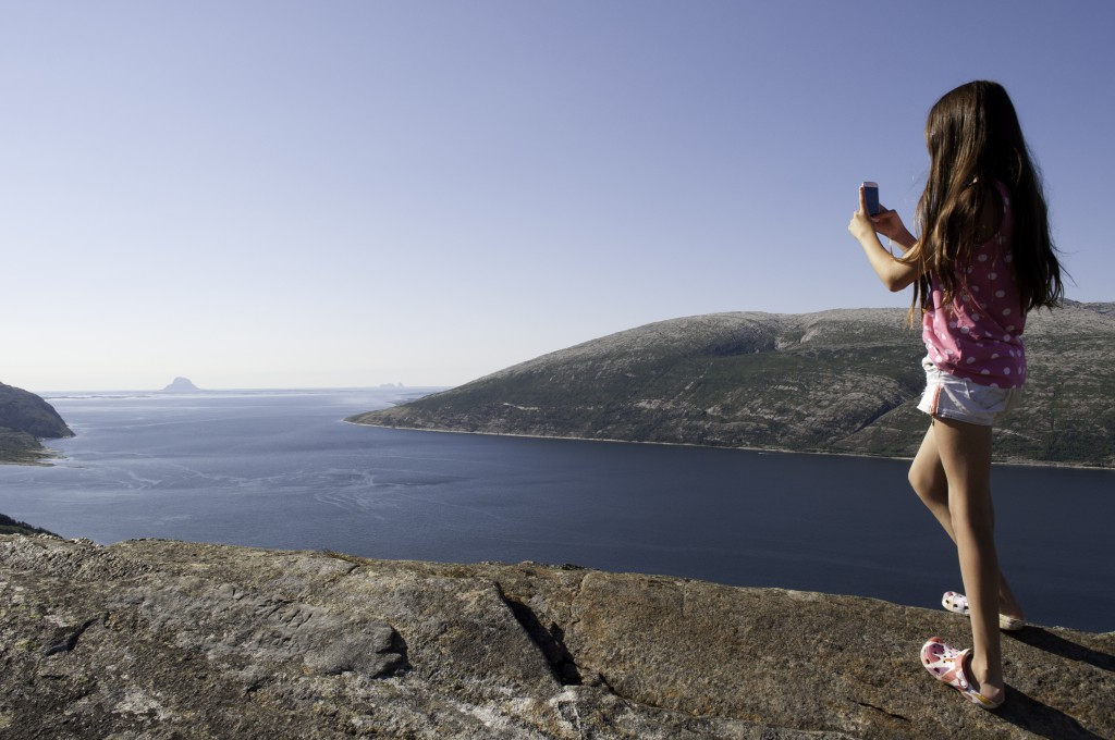 5595768-girl-photographing-fjord-in-norway